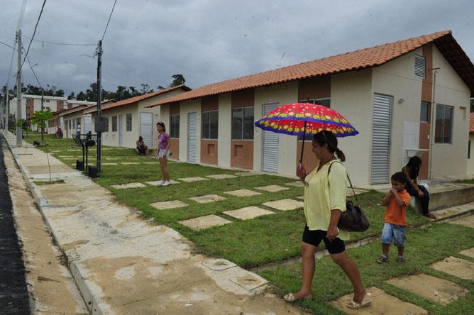 Sem sombra, mulher usa guarda chuva no conjunto do Minha Casa. (Foto: Alberto César Araújo)