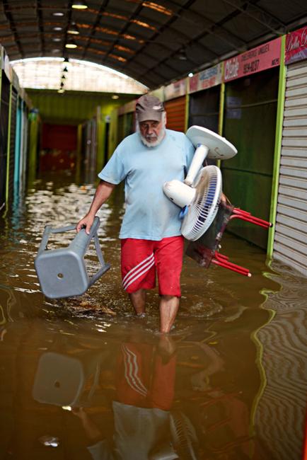 O comerciante João Genil deixou seu ponto comercial por causa da enchente  (Foto: Gabriel Ivan)