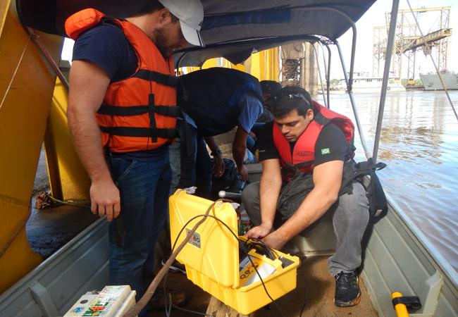 Andre Luis dos Santos (sentado) em operação no rio Madeira (Foto: CPRM)