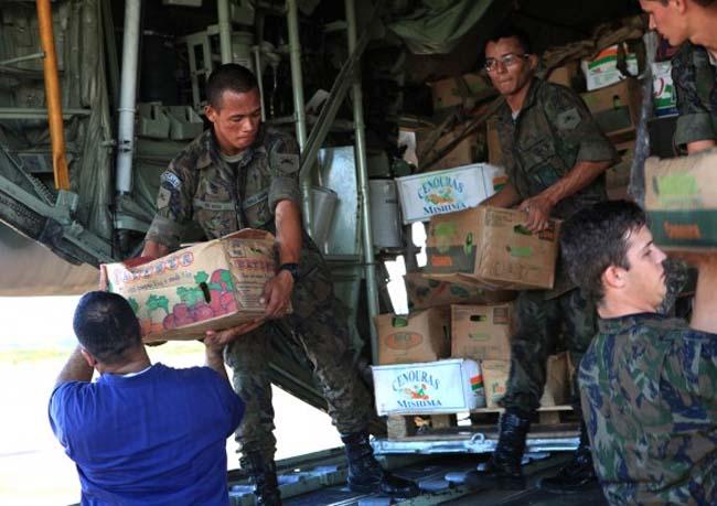 Militares da FAB descarregam cenouras dos supermercados do Acre (Foto: Sérgio Vale/Secom)