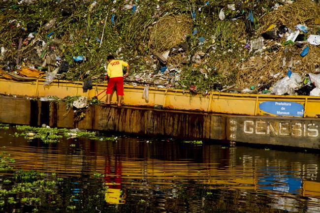 Funcionário da prefeitura retira o lixo do leito do igarapé São Raimundo, em Manaus (FotoAmazonas: Alberto César Araújo)