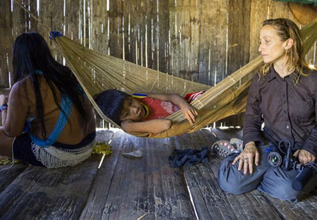 Céline Cousteau observa menino doente da aldeia Matis Tawaya no Vale do Javari (Foto: Michael Clark)