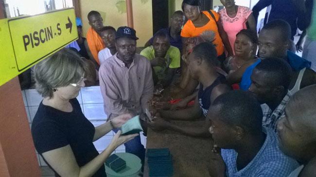 Imigrantes haitianos e senegales recebem documentos de funcionária da imigração (Foto: Freud Antunes/AR)