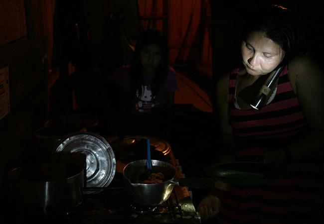 Sem energia, Maitá prepara a comida com lanterna (Foto: Odair Lima/AR)
