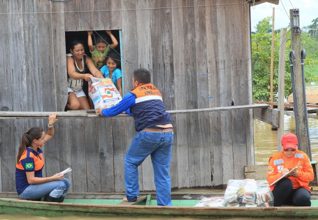 Agentes da Defesa Civil usam canoa para entregar alimentos as famílias em Canutama em 2015 (Danilo Mello/FotoAmazonas)