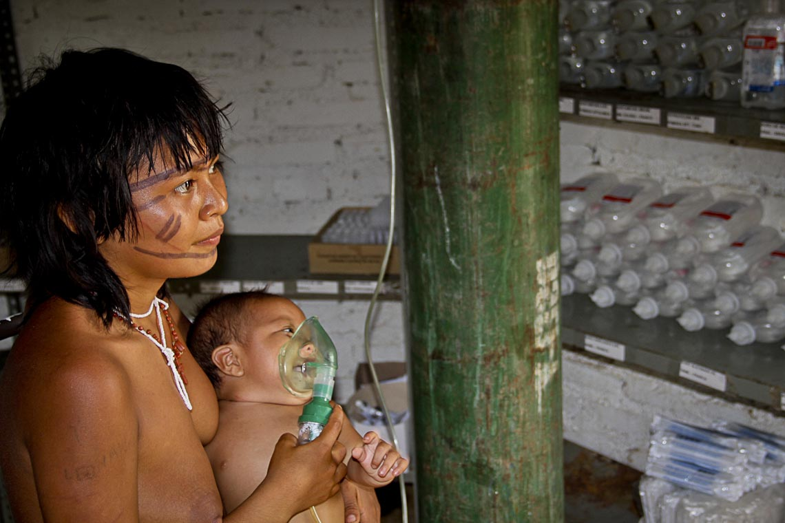No colo da mãe, criança yanomami com problema pulmonar por causa da fumaça. (Foto: Prevfogo/Ibama-RR)