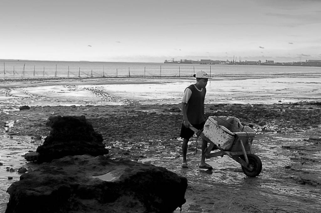 Pescadores trabalham na Praia do Cajueiro, no horizonte o Porto de Itaqui (Foto: Ana Mendes/Amazônia Real)