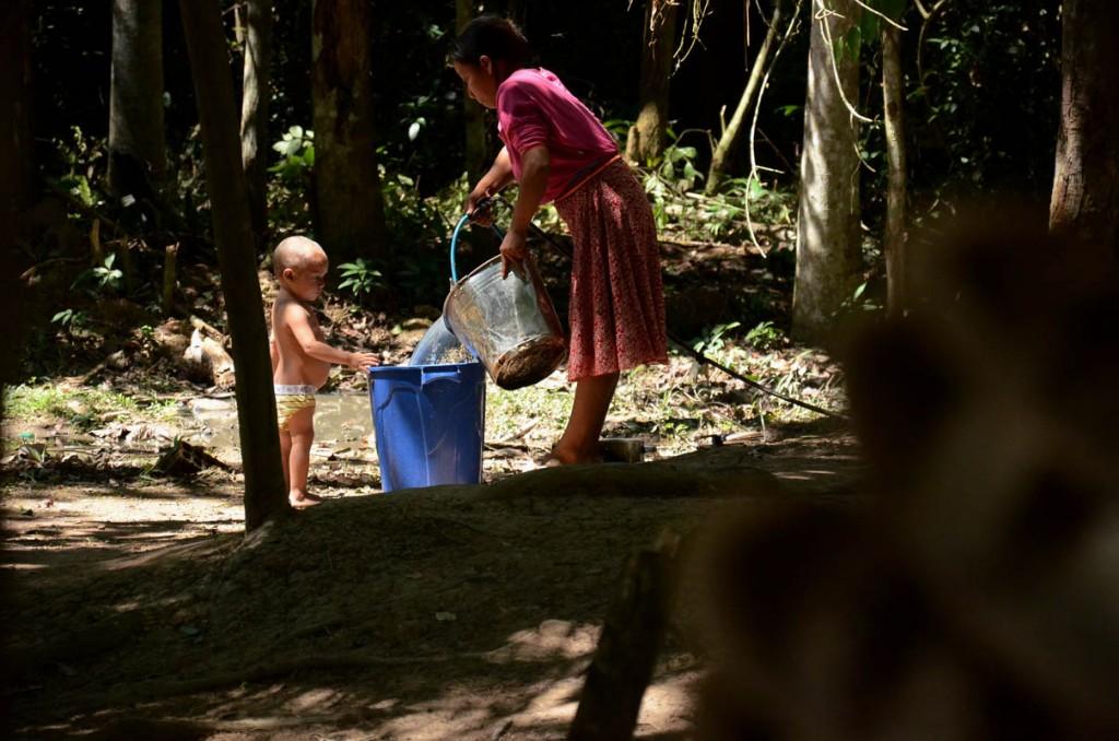 Mulher Huni Kuin  retira água do poço no Parque Ambiental de Plácido de Castro. (Foto: Odair Leal/AmReal)
