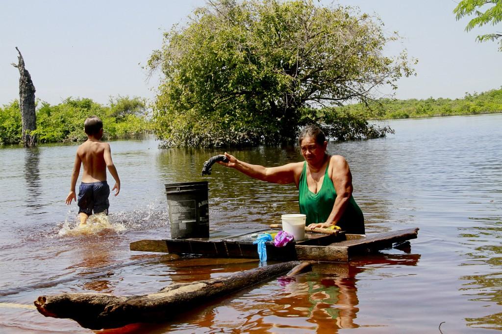Dona Jeremias de Souza Tavares lava roupas no quintal de casa, o igarapé Tarumã-Mirim (Foto: Alberto César Araújo/Amazônia Real)