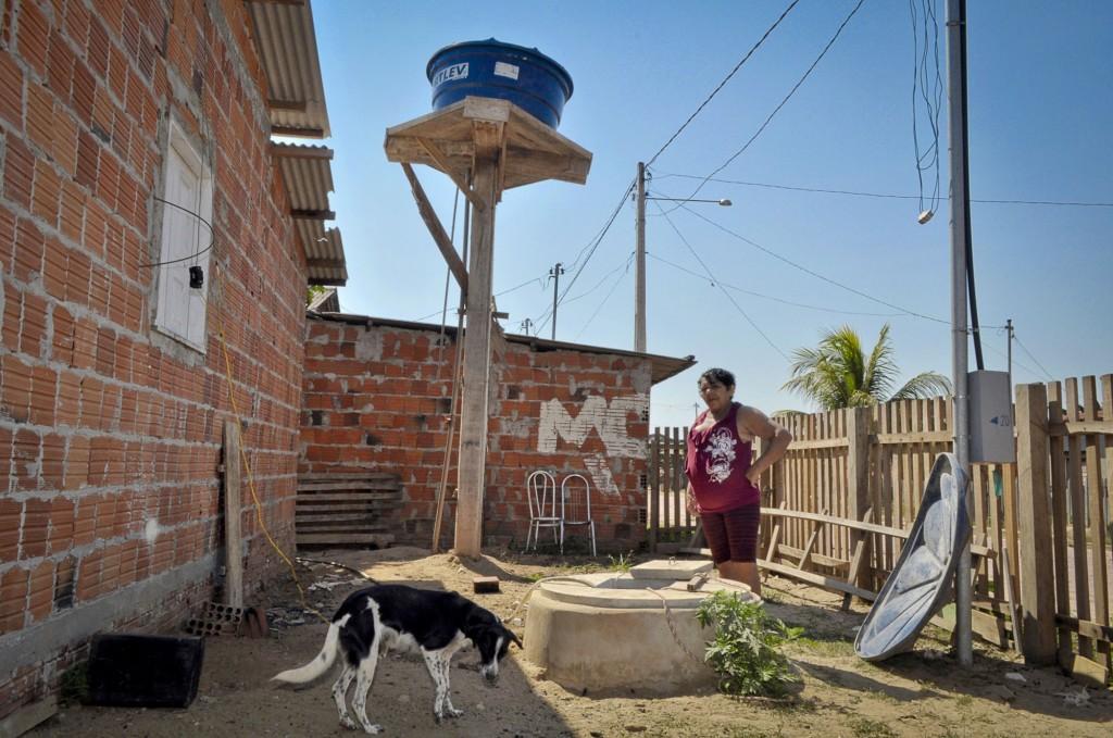 A moradora Maria Izelda da Silva paga para encher a caixa d´água (Foto: Odair Leal/Amazônia Real)