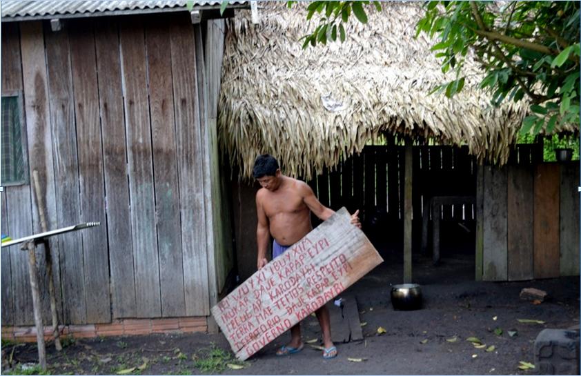 """Cacique Juarez Saw Munduruku com uma placa preparada para marcar o local sagrado """"Travessia dos Porcos""""."""