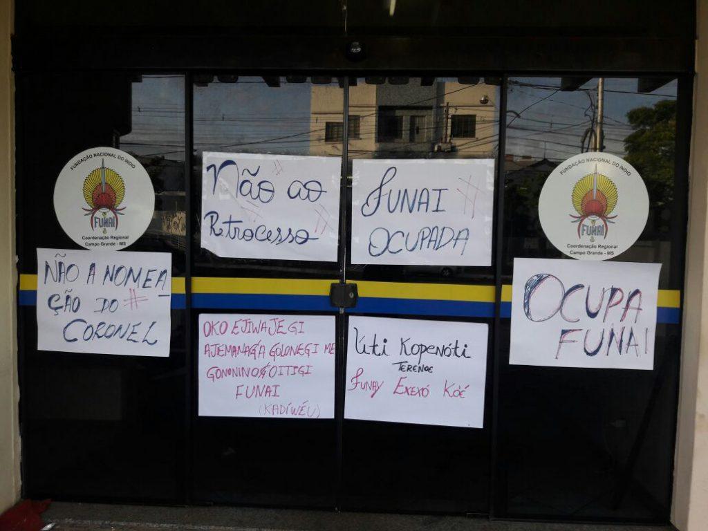Cartazes mostram a oposição à nomeação do coronel (Foto: Hekere Terenoe)