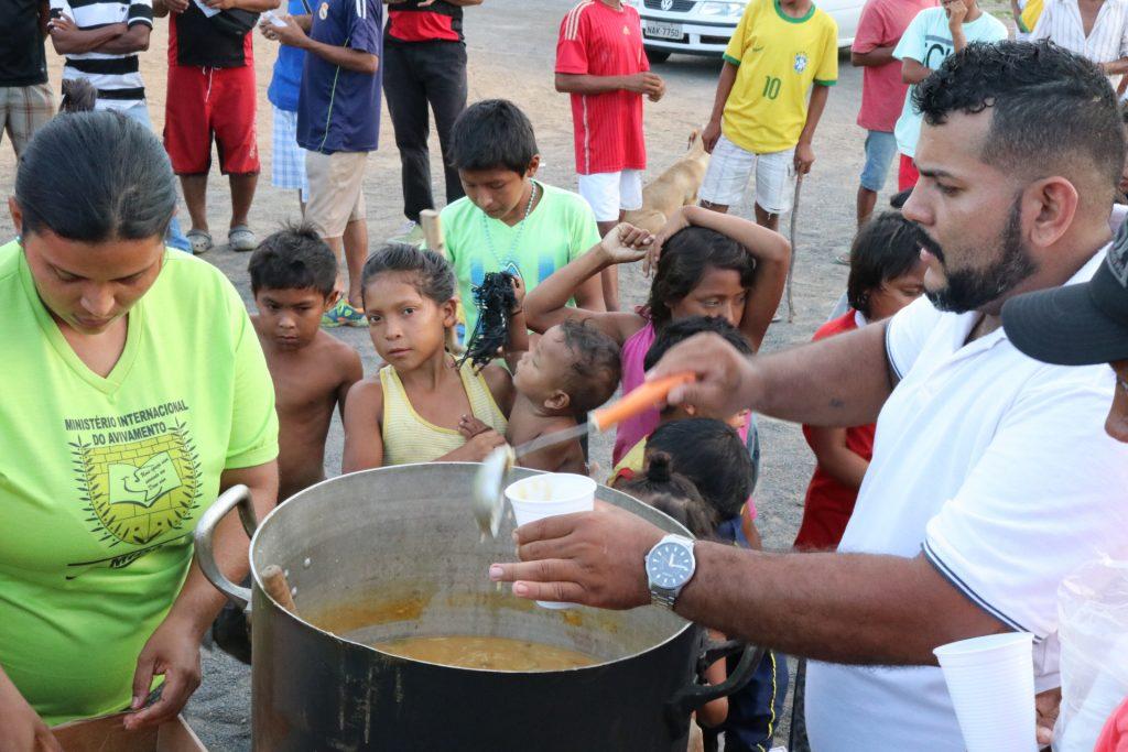 Voluntário entrega sopa para migrantes Warao em Boa Vista (Foto: Vandré Fonseca/Amazônia Real)